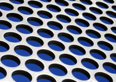 20427911 - aluminum perforated grid against a blue sky under sun light
